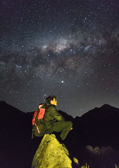 Low angle view of man standing on mountain against sky at night