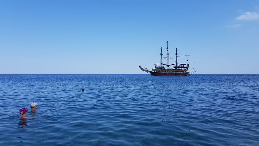 Scenic view of sailboat in sea against clear sky