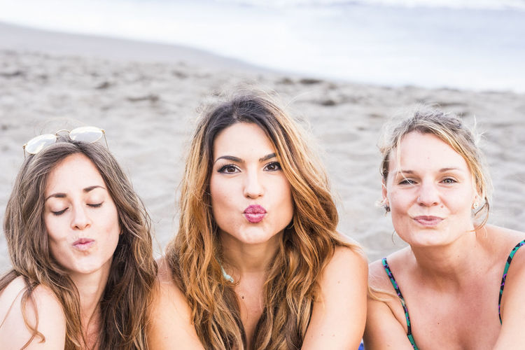 Female friends puckering while sitting at beach