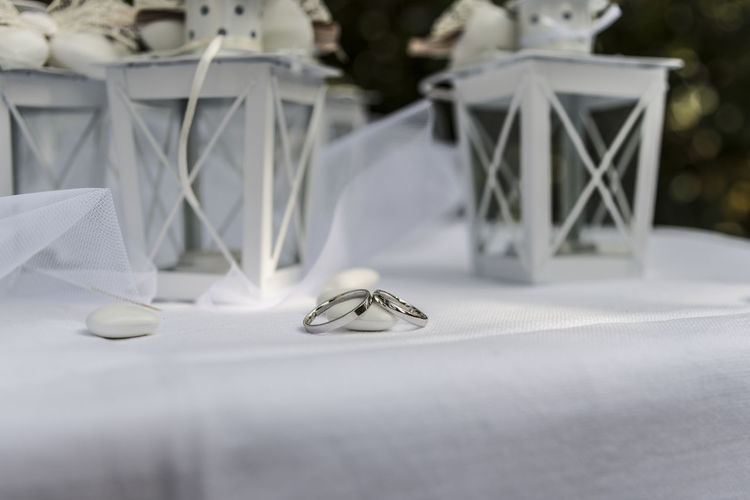 Close up of Wedding rings near comfits and wedding favors Table Wedding Celebration Still Life Indoors  Event No People Selective Focus Paper Wedding Ring Love Jewelry Ring Life Events White Color Emotion Focus On Foreground Close-up Positive Emotion Decoration Silver Colored Luxury Personal Accessory