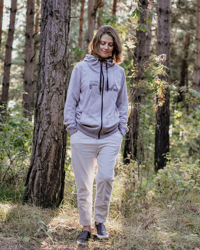 Casual Clothing Day Forest Front View Full Length Hairstyle Hands In Pockets Land Leisure Activity Lifestyles Nature One Person Outdoors Plant Portrait Real People Standing Tree Tree Trunk Trunk WoodLand Young Adult
