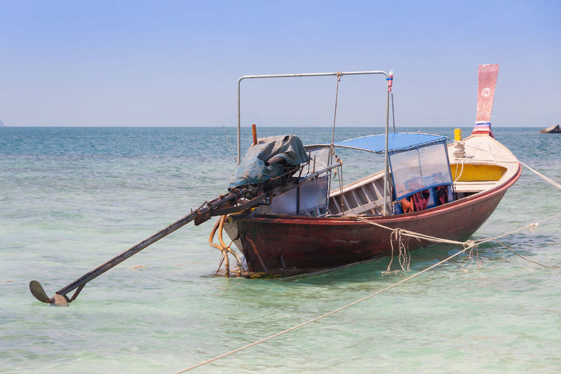 Fishing boat moored in sea against clear sky