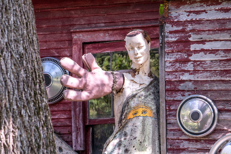 hey can I give you a hand? a large hand on an old figure creates a comical scene at a fun salvage yard in Michigan usa Figure Dummy Maniquin Man Statue Large Hand Give Me A Hand Please Comical Humor Humorous Outdoors Human Representation Faded Old Beat Up Nature Perspective Junk Yard Art