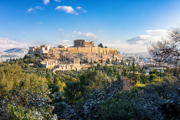 The snow covered Acropolis Hill in Athens, Greece, with the ancient Parthenon Temple on a winter day Scenics - Nature History Tranquil Scene The Past Building Exterior Sky Outdoors Day Mountain Built Structure Architecture Athens Greece Acropolis Parthenon Ancient Plaka Sightseeing Landmark Winter Snow Sunny Cold Blue Beauty In Nature