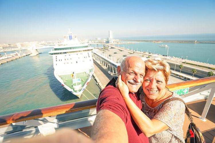 Portrait of senior couple on boat against sky