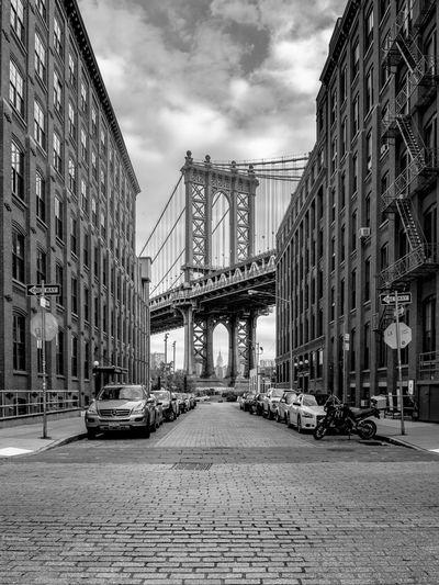 Cars Parked On Street Against Manhattan Bridge
