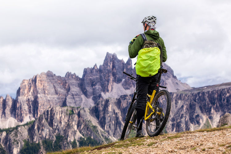 Rear view of person with bicycle on mountain against cloudy sky