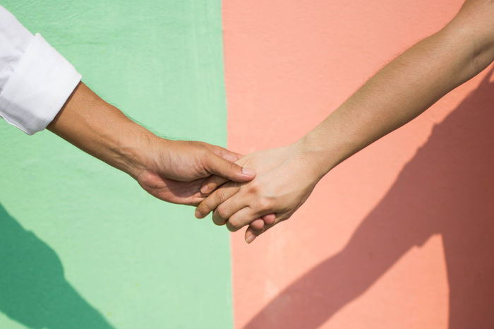 Cropped image of people with holding hands against wall