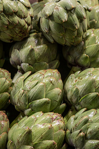 A full frame photograph of artichokes for sale at a farmers market