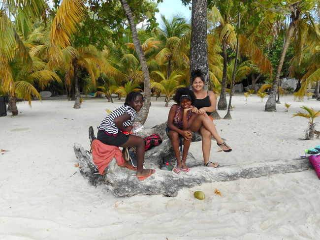 Honduras Bay Islands Beach Day Enjoyment Front View Happiness Leisure Activity Lifestyles Looking At Camera Mid Adult Mid Adult Men Mid Adult Women Outdoors Portrait Real People Sand Sitting Smiling Togetherness Tree Vacations Young Adult Young Men Young Women