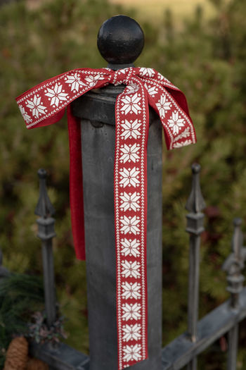 Christmas ribbon, pine garlands, pine cones, decorate a vintage outdoor wrought iron fence Focus On Foreground Day Belief Religion Spirituality Cross Red No People Nature Outdoors Close-up Christmas Decoration Christmas Ornament Wrought Iron Christmas Ribbons Outdoor Christmas Decoration Fence Holiday Background Vintage Christmas Decorations Red Ribbon Pine Cones Decorations Pine Cones Christmas Decor