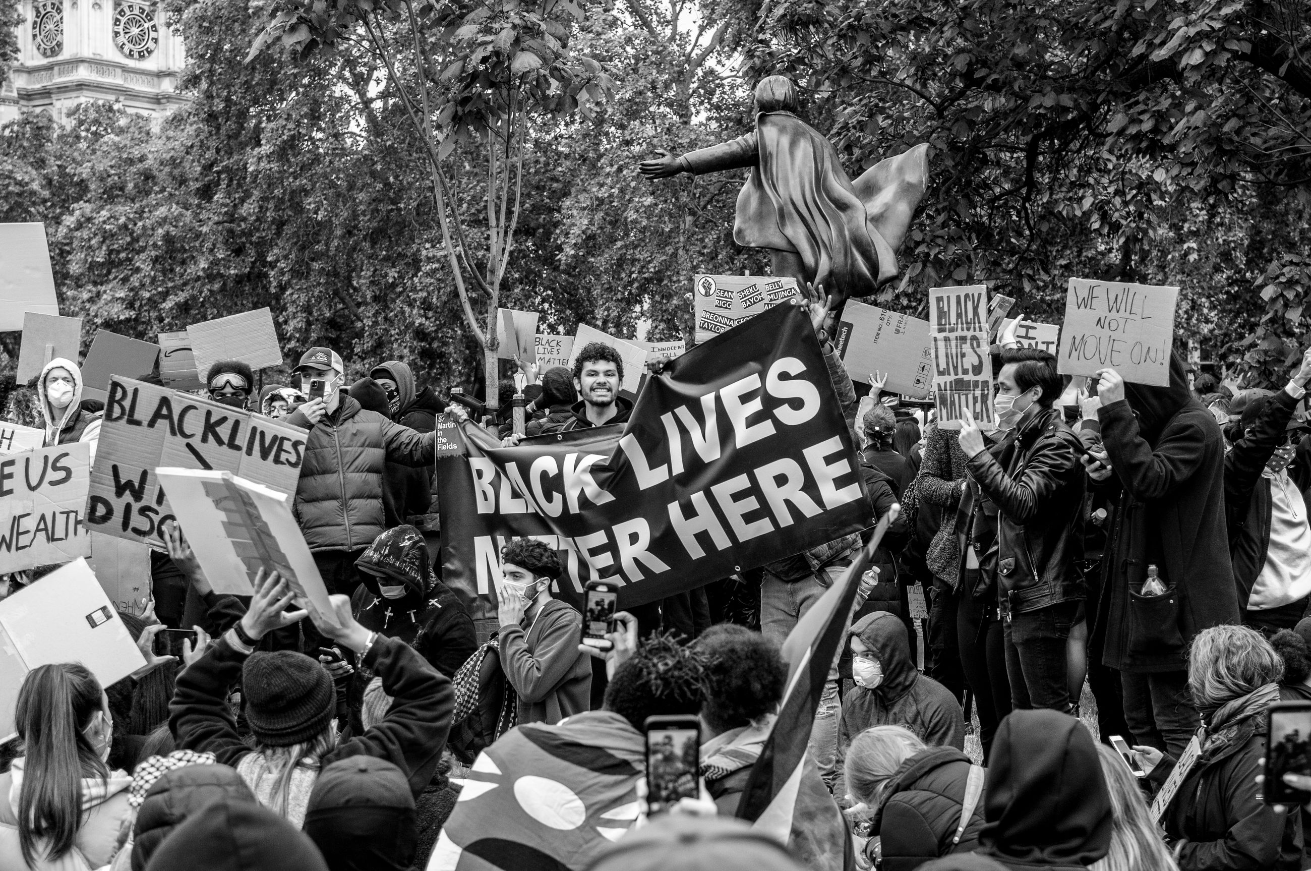 crowd, protest, black and white, large group of people, group of people, protestor, monochrome, tree, monochrome photography, day, men, women, text, clothing, adult, plant, architecture, outdoors, person, city, communication, street