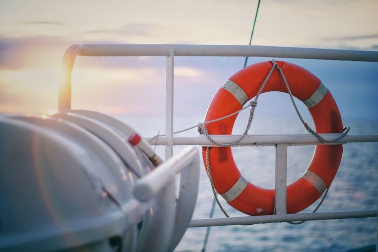Life belt hanging on boat in sea during sunrise