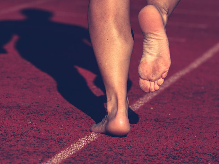 Solid bare feet of hard training woman. a woman runs along soft surface of a running track in pants