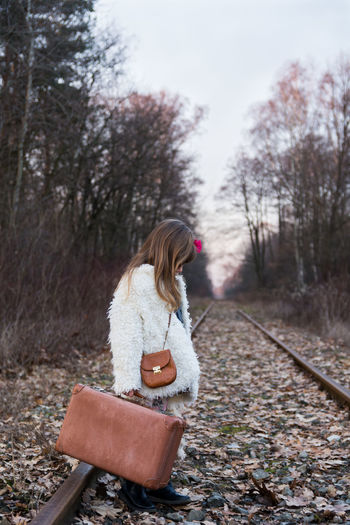 Girl Holding Suitcase While Standing On Railroad Track