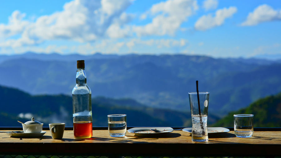 Bottles on table by mountains against sky