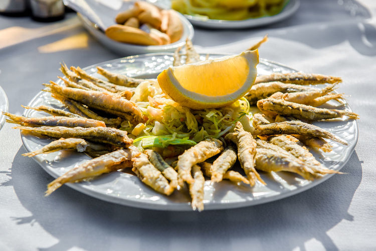 Plate of deep fried anchovies with lemon and salad Andalucía Culinary Dinner Lunch Malaga Nerja Spain Prepared Fish Seafood Anchovies Close-up Costa Del Sol Day Deep Fried  Delicious Food Lemon No People Outdoors Outdoors Cafe Plate Portion Ready-to-eat Restaurant Spanish Cuisine Sunny Day