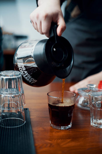 Close-up of hand pouring coffee in glass