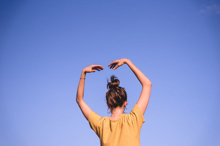 Rear view of woman dancing against clear blue sky