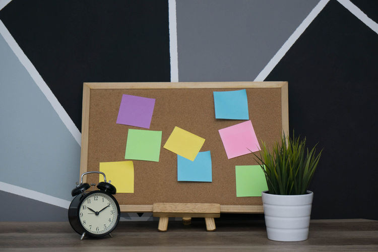 Bulletin board with colorful blank adhesive notes by alarm clock and potted plant on table against wall