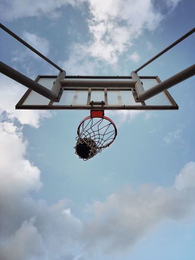 Low Angle View Of Basketball Ball In Hoop Against Sky