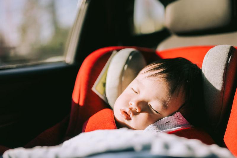 Cute boy sleeping in car