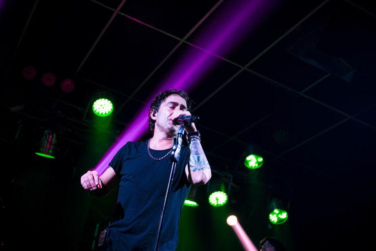 Man singing on illuminated stage at night