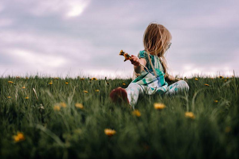 Girl picking flowers on field