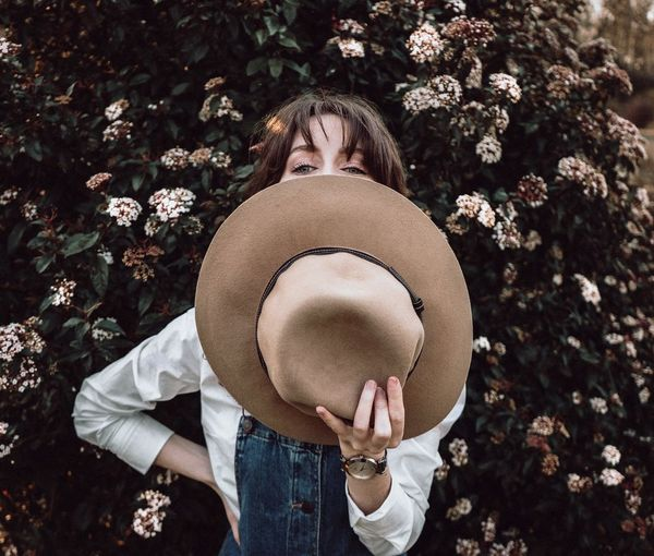 Young Woman Holding Hat While Standing Against Plants
