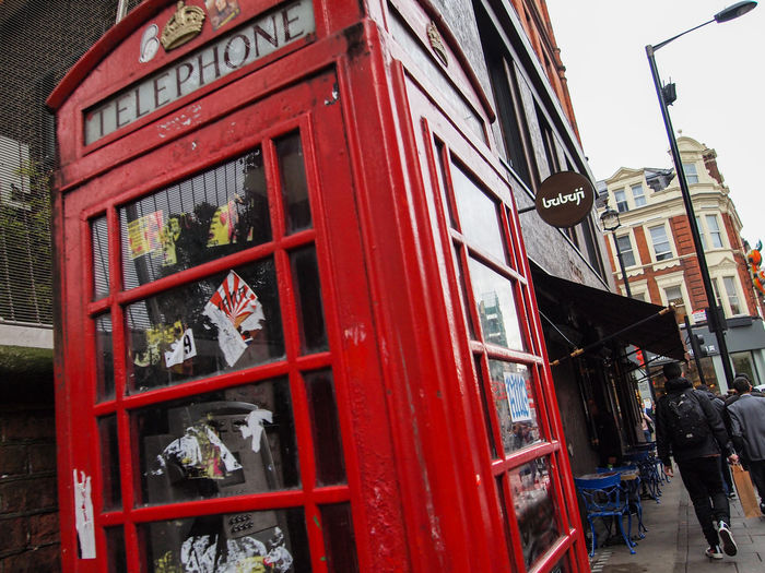 City Cloudy Day Day Different Perspective England English Nostalgia Nostalgic  Outdoors Red Red Booth Street Streetphotography Telephone Telephone Booth Text Vandalism