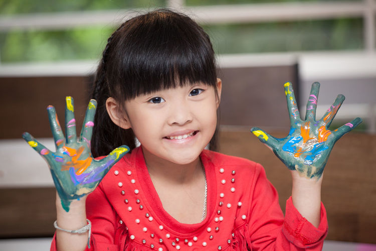 Portrait of smiling girl with painted messy hands