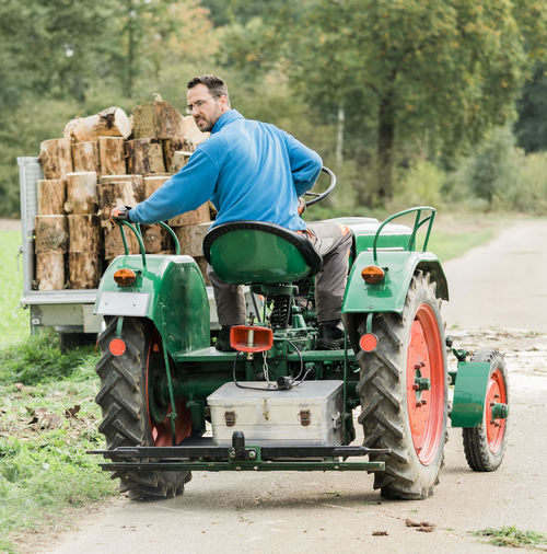 Full length of man driving tractor on road