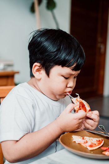 Cute boy eating food at home