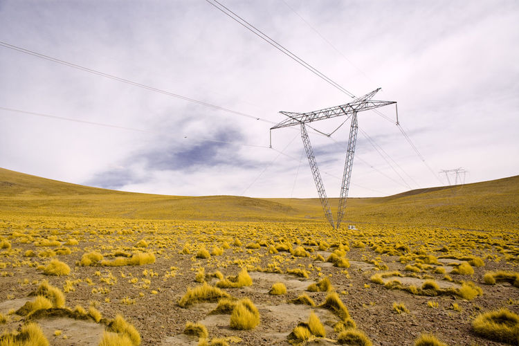 Low angle view of electricity pylon on field against cloudy sky
