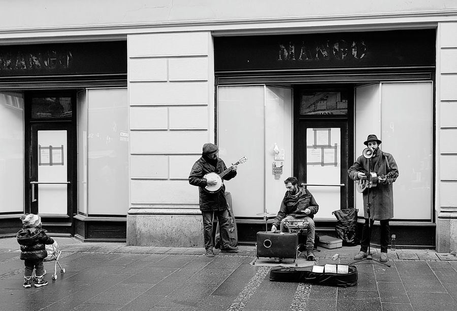 Street musicians and an observer. Performance Group Musicians Life Little Girl Arts Culture And Entertainment Day City