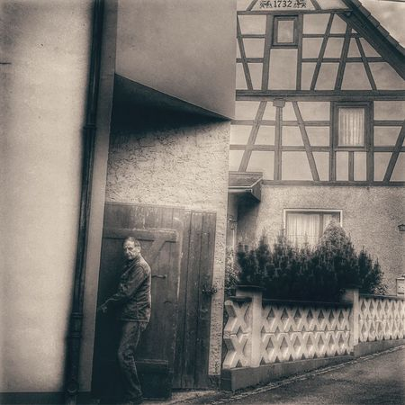 Man opening a door in vintage style and black and white , very old architecture behind Architecture Building Exterior One Person Built Structure Real People Full Length Day Outdoors Men People Strange Stranger Unique Man Old Door Architectureporn Architecturephotography Architecture_collection Scene Black And White Book Cover Great Impressive House Art Is Everywhere Cut And Paste The Street Photographer The Street Photographer - 2017 EyeEm Awards