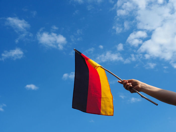 Female hand with a German flag Females German Blue Body Part Cloud - Sky Day Finger Flag Germany Hand Holding Human Body Part Human Hand Human Limb Leisure Activity Lifestyles Low Angle View Multi Colored Nature One Person Outdoors Real People Sky Unrecognizable Person