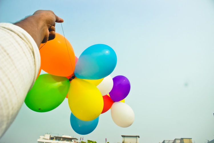 Cropped Hand Of Man Holding Multi Colored Balloons Against Sky