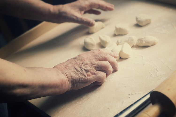 Close-Up Of Hands Kneading Dough On Table