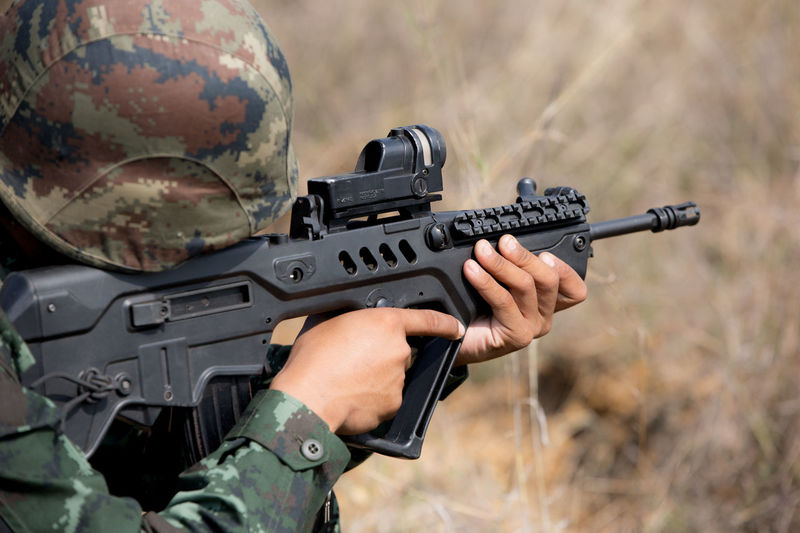 Close-up of army soldier aiming with rifle