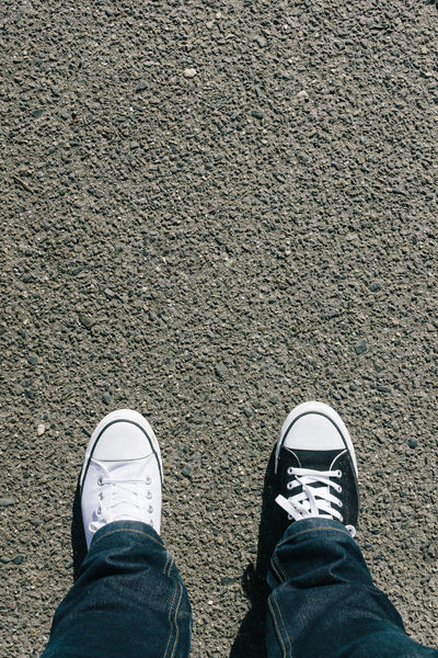 Black and white shoes on asphalt texture, personal perspective Asphalt Black And White Canvas Shoe Difference  Flortraits Footsie Grey Human Leg Men One Person Opposites Outdoors People Personal Perspective Same Same But Different Shoe Shoes Standing