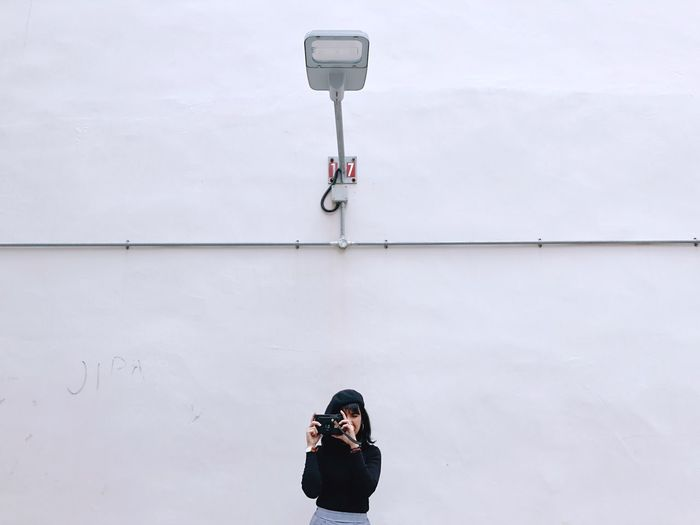 Young Woman Photographing Against Wall