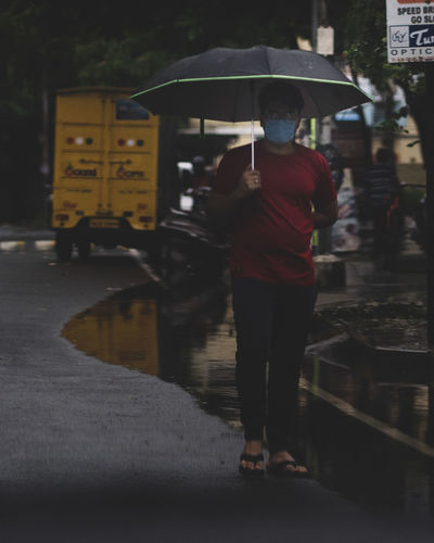 Rear view of man standing on wet street in rainy season