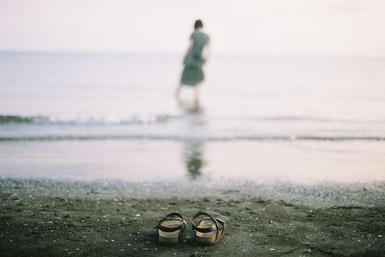 Close-Up Of Sandals On Shore At Beach Against Woman In Sea