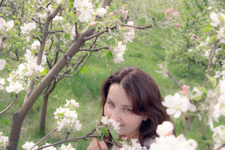Portrait of woman against white flowering plants