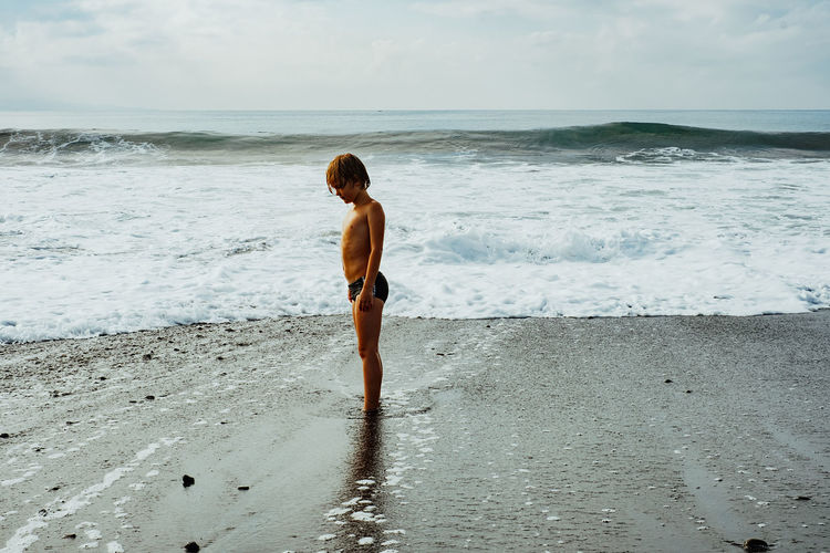 Side view of shirtless boy standing at beach