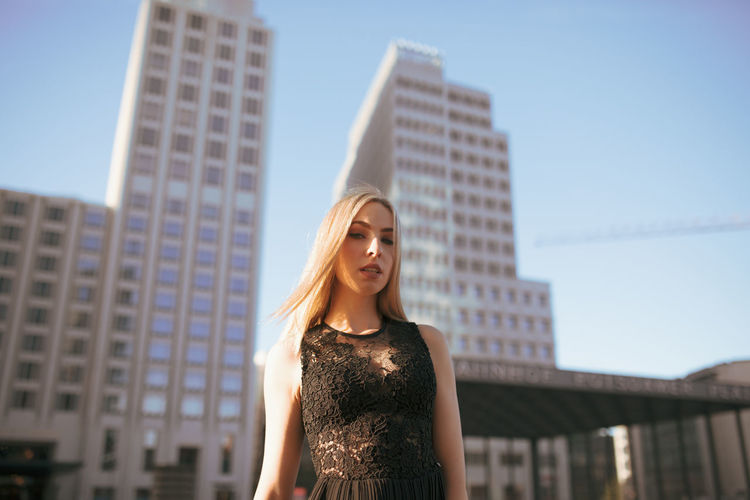 Portrait of beautiful woman standing against buildings