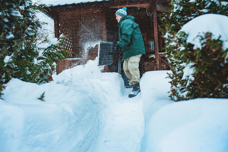 Man removing snow with shovel outside house