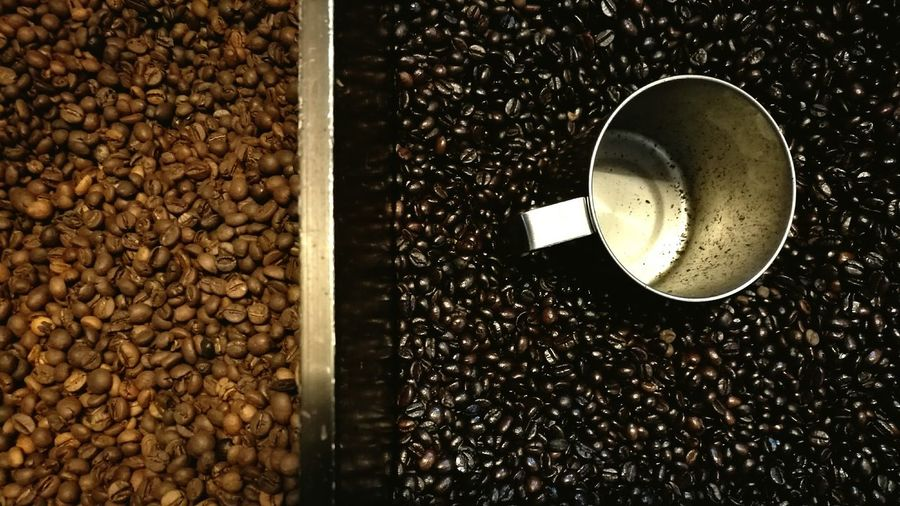 High angle view of container on roasted coffee beans