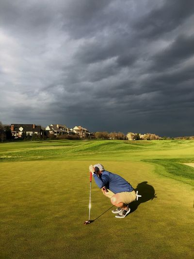 Man on golf course against sky